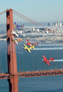 Six of the world's best aerobatic pilots pass by in formation in front of the Golden Gate Bridge.
