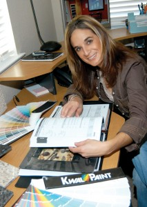 Jessica Padilla, owner of Project Professional, at her desk with her interior design swatches.
