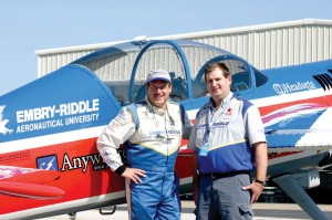 Eric Beard and his assistant pose alongside Beard's Yak 54.