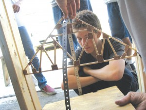 """Doug DeVicariis anxiously looks on as his truss design is tested for its weight bearing capabilities."""""""