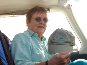 "Audrey Wells displays the ""Mercy Pilots of Orcas"" baseball cap given to her by one of her passengers. On it are her FAA WINGS program, Ninety-nines and AOPA pins."