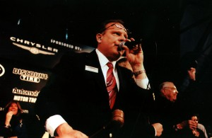 "Head auctioneer ""Spanky"" Assiter, gavel in hand, calls the auction of the first 2007 Shelby G.T. 500, while an elated Carroll Shelby waves his hat to the bidders."