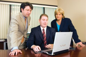 CEO Roger Woolsey(left), CFO Terry Cross and Sandy Nelson, VP of marketing,use the FBO's security system to view real-time activity on a laptop computer.
