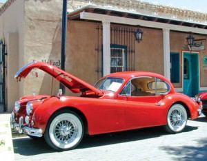 A 1950s XK-series Jaguar poses futuristically in front of an early adobe building.