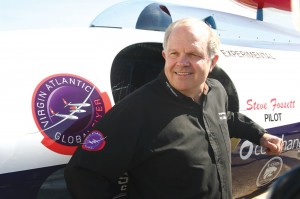 Steve Fossett points out the mission patch on the fuselage of the Virgin Atlantic GlobalFlyer that accurately depicts how the aircraft looks in flight.