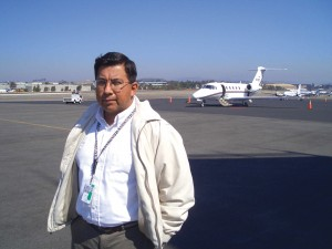 Willy Vazquez on tarmac with jet in background: Willy Vazquez got his aviation start in aircraft safety maintenance.