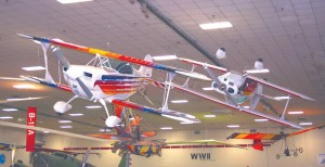 "Hanging prominently over the entrance area to Wings Over the Rockies is a Christen Eagle and a Pitts biplane in aerobatic flight. Slightly beyond, the fascinating Flying Machine from Disney's ""Around the World in 80 Days"" captivates visitors of all ages."