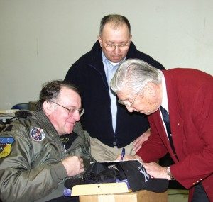 Legendary test pilot Scott Crossfield signs a copy of a book about his flying exploits for fan Larry Johnson (left) of Vancouver, Wash., and Joel Hernandez.