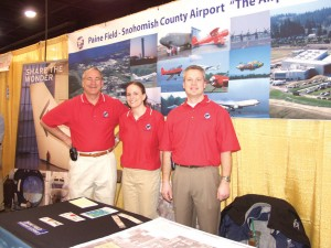 L to R: Director Dave Waggoner, operations staffer Kara Underwood and operations superintendent Bruce Goetz represented Paine Field at the aviation conference. The booth included display space for the Future of Flight center in Everett.