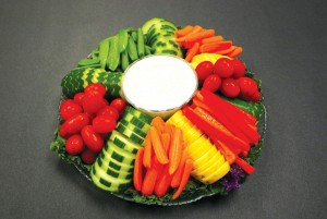 A colorful vegetable tray includes grape tomatoes, snap peas, long-stem broccoli, baby carrots and bell peppers, accompanied by Amina Halim's homemade mint yogurt dipping sauce.