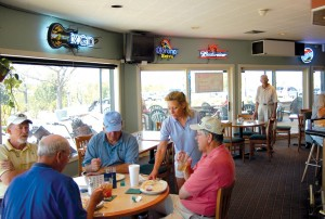 Bill Richardson enjoys lunch with his friends after a round of golf while Tina Sullivan, bartender, takes their empty plates.