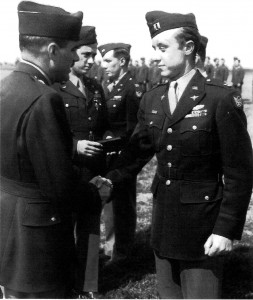 "Captain Harold E. ""Bunny"" Comstock receives a medal in 1943. At his right is Dave Schilling (holding a box). Comstock served 30 months and two tours; he finished his second tour as the commanding officer of the 63rd Fighter Squadron, with 136 missions."