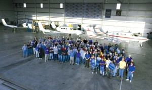 Some of Adam Aircraft's 300+ assembly facility staff pose in front of the company's first two prop-driven A500s.