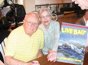 "Capt. Clayton Kelly Gross, with his charming wife Ramona, signs his newly released book, ""Live Bait."" During World War II, he had six victories to his credit."