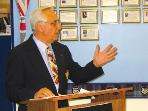 Roy Thompson, board chairman and museum director, speaks to about 50 guests at an open house for the media in late May. Thompson, considered to be a historical expert on planes of the past, is a former major in the Canadian Air Force.