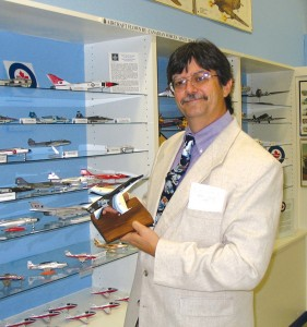 Tom Grossman, the museum's model program director, displays some of the military planes he built for the museum.