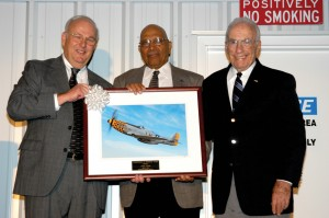 "Museum founder David O'Maley (left) presents the first of two identical ""2006 Contribution to Freedom"" awards to Tuskegee Airmen Bob Lehr (center) and B-17 pilot Herb Heilbrun. The photo is of the museum's P-51D Mustang, similar to that flown by Lehr."