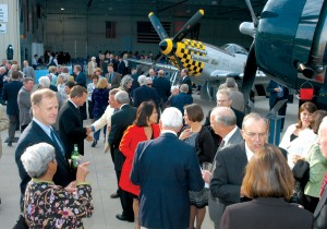 Reception guests mingled amongst a ramp full of warbirds displayed outside the hangar dinner, including Cincinnati Miss (visible in background), Tri-State Warbird Museum's striking P-51D Mustang.