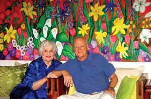 "Artists Louise McCall and Bob McCall relax beneath one of her paintings, which she calls ""The Garden."""