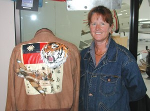 Terri Polley stands beside the leather jacket she painted to honor Erik Shilling, one of the legendary Flying Tigers.