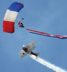 The Goodrich Waco, flown by air show veteran Bob Wagner, circles a Liberty parachute team member during the opening ceremony.