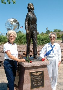 Carol Hamilton and Dorothy Swain Lewis stand beside the WASP Tribute. The tribute sits on a red granite base, below a World War II Memorial Globe.