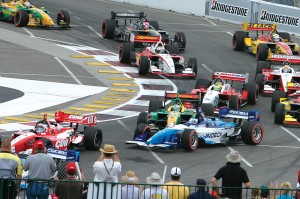 The fifth annual GPD offered excitement for spectators. On turn one, lap one, Alex Tagliani (green/yellow) bumped Paul Tracy (blue/white). Tagliani was out of the race, while Tracy spun, placing him last. He would eventually run as high as second place.