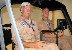 Kent Slater, general manager of the Silver State Training Center, and flight instructor Adam Grim (right) demonstrate the school's R22 flight simulator.
