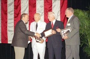 Harry Combs shakes hands with Dan Patterson, 2003 Combs Award winner, as fellow NAHF enshrinees Gene Cernan and Neil Armstrong look on. The award, which will again be presented during NBAA's annual convention, has been renamed the Combs Gates Award.