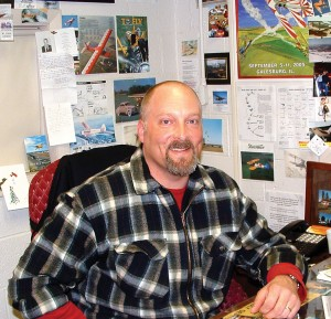 John Chmiel has covered his office walls with aviation memorabilia. His enthusiasm for all things flight-related is evident in his office, and from spending just a few moments talking with him.