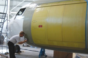 Mike Sotherden, chief mechanic, completes the final touches to the cargo door installation. This involves removing the existing three-foot-wide door and installing one that is nine feet wide.
