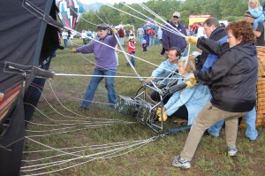 While sitting in the basket, Mary Ann Hawkins heats the air in her balloon, Chameleon II. Assisting her is her crew, plus Carol Garland (left), fellow balloonist.