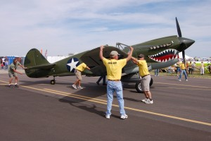 Ground crews busily positioned aircraft, such as the P-40 Warhawk, on the airport ramp.
