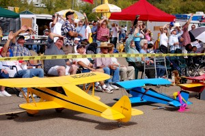 Planes used in the radio controlled aircraft demonstration sat on the ramp while spectators watched the real airplanes perform overhead.