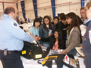 Students had hands-on experiences at the career expo. Here, an EMT demonstrates how a small blood pressure cuff works on a student's finger.