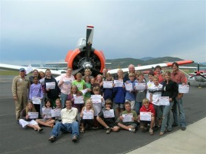 Students proudly display their certificates of achievement in front of a vintage T-6 aircraft in Steamboat Springs. Their teacher was so impressed she plans to bring her class on a field trip to Wings Over the Rockies this fall.
