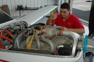 Mechanic Adrian Arias makes an adjustment on an engine.