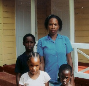 A young Haitian mother and her three children in front of their brand new home. These homes come with simple amenities we take for granted, such as doors and windows.