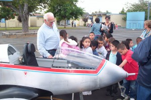 John Lewis helps children climb into a kit-built BD-5J tiny jet. They were allowed to operate the rudder, elevator, flaps and landing gear.