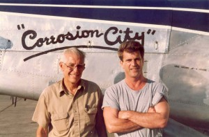 "Tom Danaher (left) in Thailand with Mel Gibson, star of ""Air America."" In the background is Corrosion City, a plane Danaher assembled from junk parts and flew in the movie."