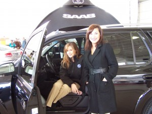 Shannon Caldwell, seated, and Shannon Sturdivant showcase a Saab 9-7X, along with the rest of the line of Saab automobiles.