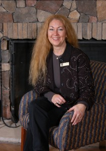 Lori Gilmore purchased the former Holiday Inn property with her two brothers, Jack and Stephen Nash. Behind her is the refurnished fireplace in the hotel lobby.