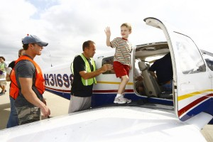 A Challenge Air participant waves from the wing before his first flight. He had his ground school training and is now ready to fly.