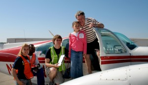 John Wing of Wing Aero, volunteer pilot and Challenge Air advisory board member, poses with Fly Day participant Jocelyn Nelson and other volunteers.