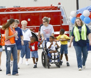 Volunteers escort a family out to the ramp. The boy is about to see the world from a new perspective.