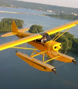 A CubCrafters Sport Cub equipped with floats cruises over Seattle and nearby Lake Washington.
