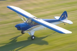 A Sport Cub in a modern paint design, instead of the Cub's traditional yellow, lands on a grassy field near Yakima, Wash.