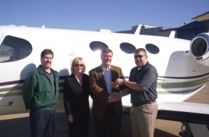 John Ballinger, Cessna customer account managers (left) and Chad Brownlee (right) congratulate Patrice and Ken Scott, Mustang Management Group owners, on their delivery of Cessna's first Citation Mustang.