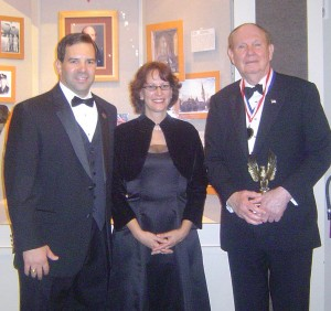 Lone Star Flight Museum President Larry Gregory (left) and museum curator Elizabeth Smith congratulate Hall of Fame inductee John F. Bookout.