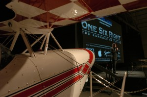 "Brian J. Terwilliger addresses the audience, standing next to a Pitts S-2B Special that appeared in ""One Six Right."""